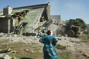 Woman watches as a house is demolished in the clampdown of illegal structures (file photo).