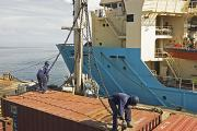 Dock workers handle containers at an African port.