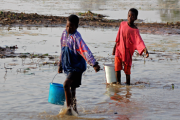 Children carrying water through a river in Ghana.
