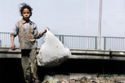 A young girl carries a bag of recyclables.