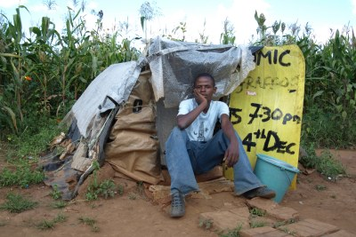A man sits outside his home in Gunhill informal settlement.