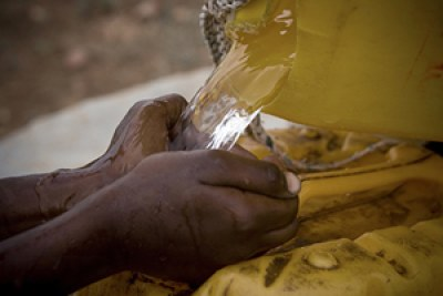 Fresh water being poured into a jerry can.