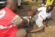 An Ivorian Red Cross volunteer providing first aid to an injured man at the scene of the violence.