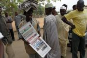 Newspaper vendor outside a polling station during the 2011 elections in Nigeria.
