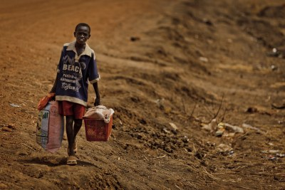 A boy carries his belongings as he flees Abyei.