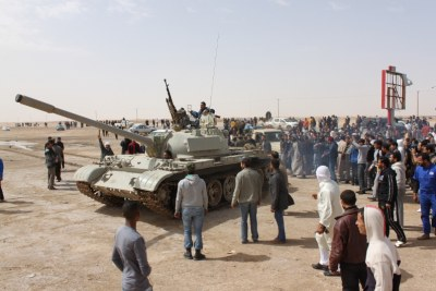 Armed rebels drive a tank past civilian onlookers (file photo).