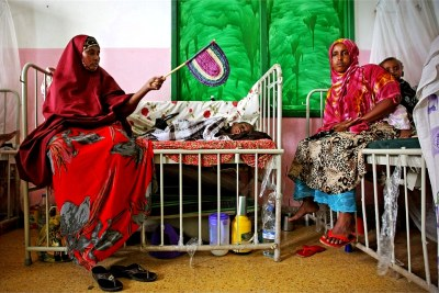 Mothers sit with their children in a hospital ward.