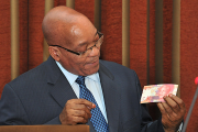 President Jacob Zuma holds the new currency bearing the image of former president Nelson Mandela.