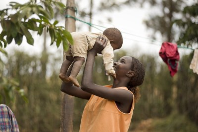 A mother plays with her young son in the Kenyan village of Mwea.