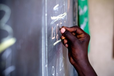 A student writes on a blackboard. Parents and teachers have lauded the governments move.