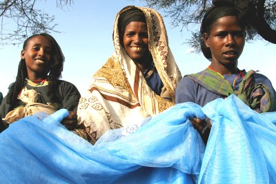 Women in Ethiopia receive free bed nets.