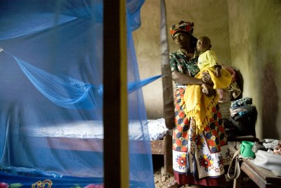 Saumo Mpotwile and her daughter, Anali,  with their bed net at the family's home in Lupiro village, Tanzania.