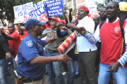 A police officer tries to control a tense situation between an angry Cosatu crowd and Democratic Alliance supporters in Johannesburg, South Africa.