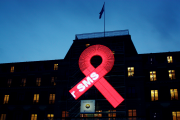 A large red ribbon is mounted on the façade of the UN Human Rights Office's Palais Wilson in Geneva, Switzerland.