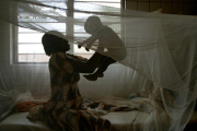 A woman and her baby under a mosquito net in Togo.