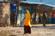 A Somali girl crosses a street on her way to school while soldiers of AMISOM's Djiboutian contingent stand guard (file photo).