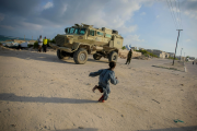 A Somali girl runs in front of an African Union armed personnel carrier in Mogadishu. In past months, residents of Mogadishu have enjoyed relative peace in their city after decades of instability.