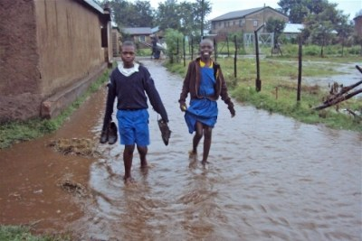 File Photo: Children walk on submerged foot paths as a result of flash floods.