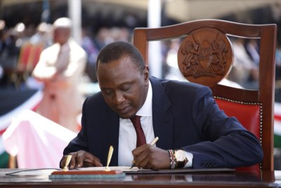 Uhuru Kenyatta signing presidential oath in front of supporters and government dignitaries.