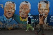Children walk past a mural of Nelson Mandela in Soweto, Wednesday, 26 June 2013. The anti-apartheid struggle icon is still in a critical condition in hospital.