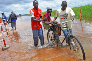 Soroti residents help an old woman to cross the flooded Awoja bridge in Teso sub region.