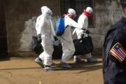 A burial team carries the body of a suspected Ebola victim under the watchful eyes of police officers.
