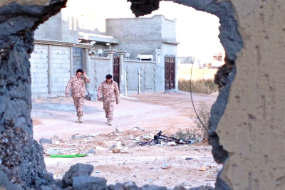 Two soldiers from forces operating under Libya's Tripoli-based government walking through the deserted streets of Bin Jawad, seen through a hole blown in the outside wall of a family home.