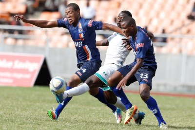 Ammy Ali,left and Mkami Himid Mao, right of Azam FC tackles Erick Ochieng of Gor Mahia FC during their Cecafa finals.