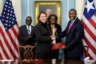 MCC CEO Dana J. Hyde, center, shakes hands with Liberian Minister of Finance and Development Amara M. Konneh (file photo).