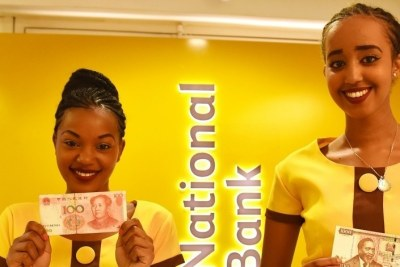 Two attendants display a Chinese currency note and a Kenyan Shilling note during the opening ceremony of a new branch of the National Bank of Kenya which will host a clearing house for Chinese renminbi (RMB) in Nairobi.