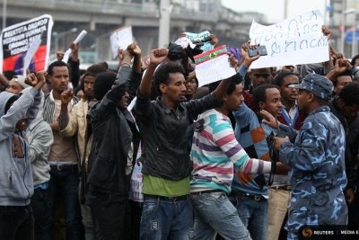 A policeman attempts to control protesters chanting slogans during a demonstration over what they say is unfair distribution of wealth in the country at Meskel Square in Ethiopia's capital Addis Ababa 9file photo).