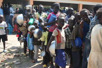 Some of the South Sudanese refugee children line up for food after arriving at Rhino Settlement Camp in Arua District in July this year