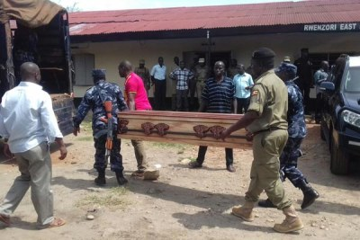 Sad send off. Police officers load coffins containing the bodies of their colleagues onto a truck to be transported to different destinations.