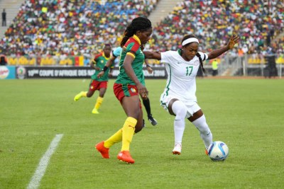 Nigerian player battles for ball against Cameroonian defender.