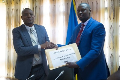 Isaac Munyakazi, the minister of state for primary and secondary education (L) receives O-Level results from Janvier Gasana, the director-general of Rwanda Education Board.